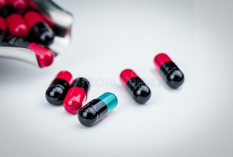 Blaugrüne Kapselpille des selektiven Fokus und Drogenbehälter mit rot-schwarzer Kapsel Globale Gesundheitspflege Antibiotikummedi stockfoto