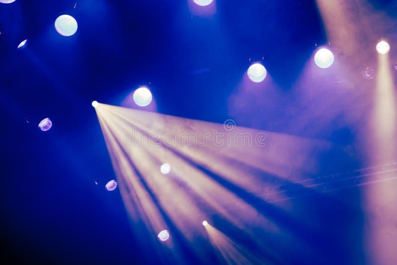 Blaulichtstrahlen vom Scheinwerfer durch den Rauch am Theater oder am Konzertsaal Lichttechnische Ausrüstung für eine Leistung od lizenzfreie stockfotografie