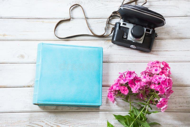 Blauw album, boeket roze flox en oude filmcamera op houten raad, hierboven Hoogste mening stock afbeeldingen