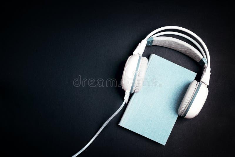 Blauw boek met witte hoofdtelefoons op het op zwarte achtergrond Au stock fotografie