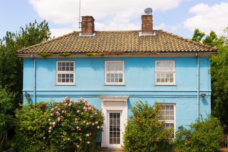 Blauw buitenhuis met witte die vensters door tuin worden omringd stock afbeelding
