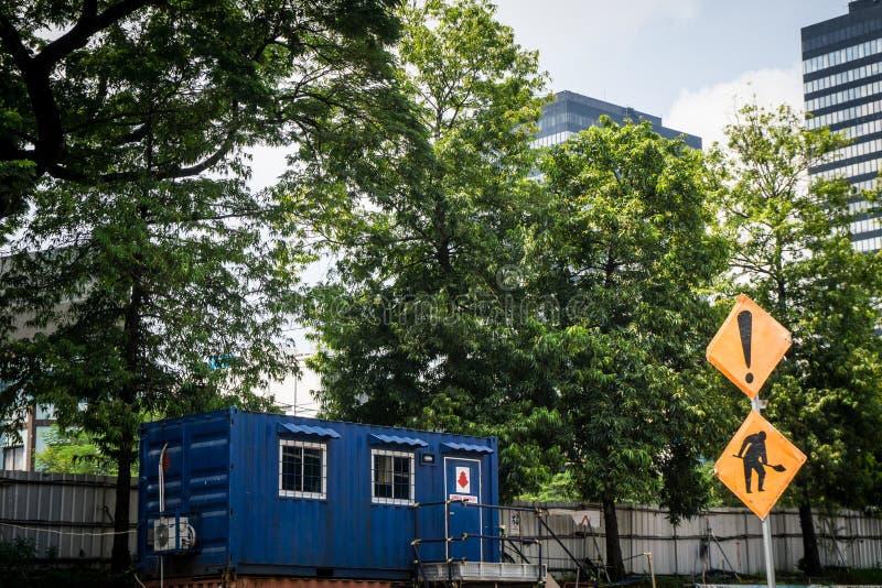 Blauw containerhuis als bureau of huis met groene boom als achtergrond en grote bouw stock afbeelding