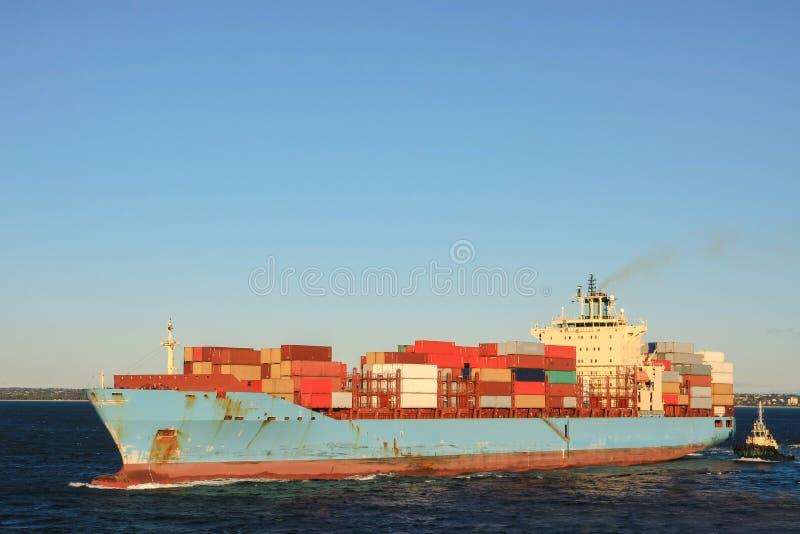 Blauw containervrachtschip op zee stock foto