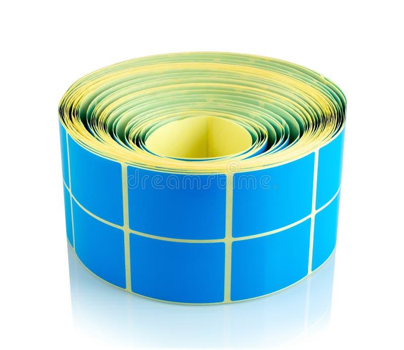 Blauw die etiketbroodje op witte achtergrond met schaduwbezinning wordt geïsoleerd Kleurenspoel van etiketten voor printers royalty-vrije stock fotografie
