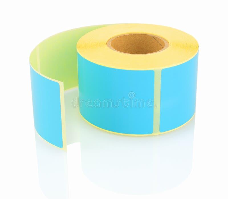 Blauw etiketbroodje op witte achtergrond met schaduwbezinning Kleurenspoel van etiketten voor printers stock fotografie