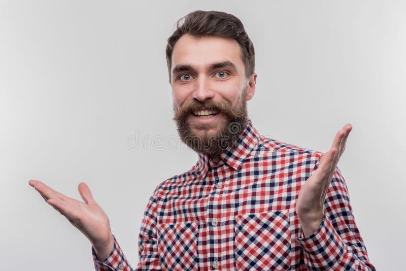 Blauw-eyed gebaarde zakenman die nieuwsgierig terwijl het nemen van belangrijk besluit voelen stock afbeelding