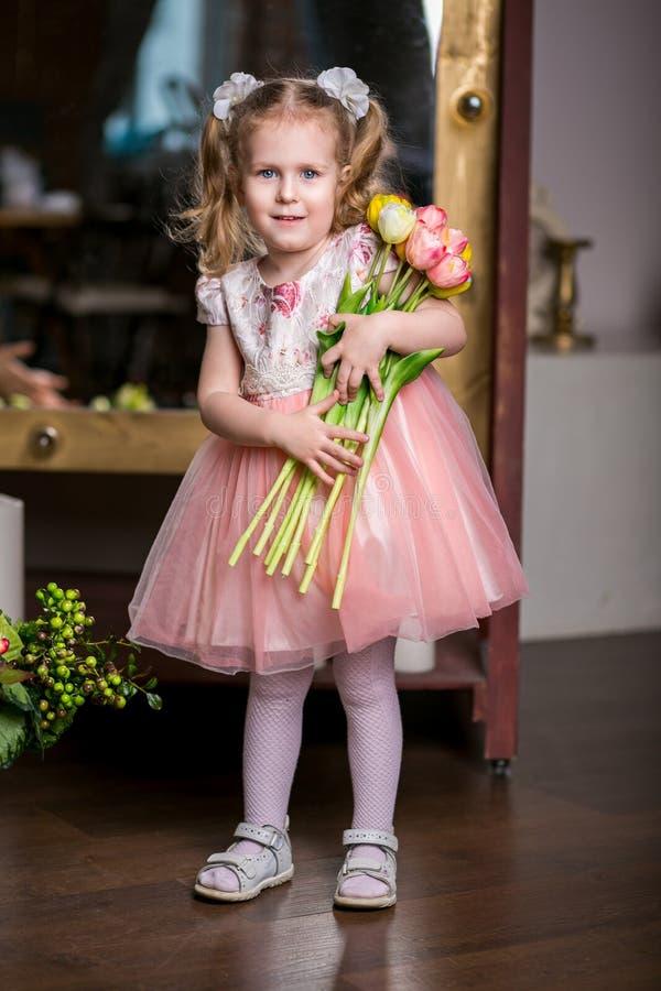 Blauw-eyed leuk meisje in een roze kledingsholding in haar handen een armvol tulpen royalty-vrije stock foto's