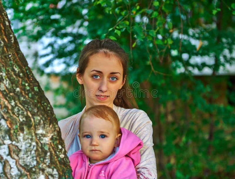 Blauw-eyed meisje met zijn jonge moeder openlucht royalty-vrije stock afbeeldingen