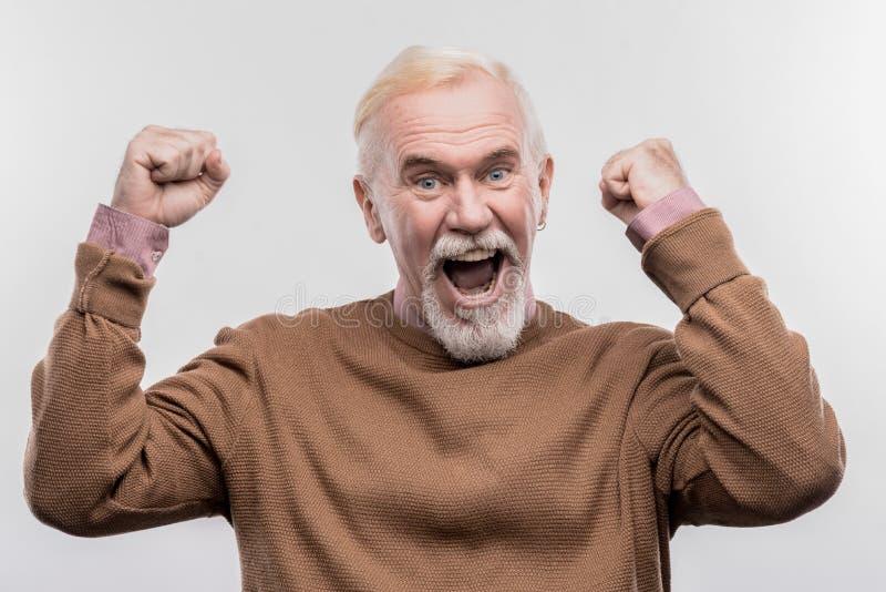 Blauw-eyed oude mens die uiterst vrolijk en gelukkig na het bereiken van succes voelen royalty-vrije stock foto's