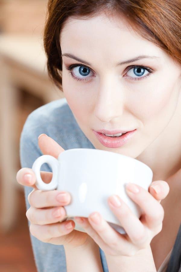 Blauw-eyed vrouw met kop thee stock fotografie