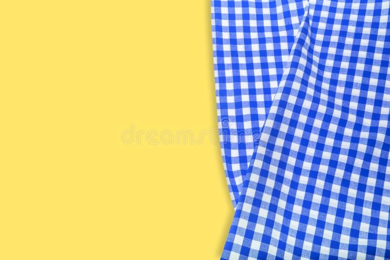 Blauw geruit servet op een gele achtergrond stock afbeelding