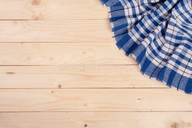 Blauw geruit tafelkleed op een lichte houten lijst met exemplaarruimte voor uw tekst Hoogste mening stock afbeeldingen
