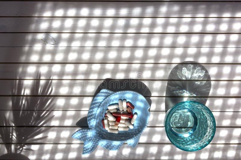 Blauw glas schone water en pillen op witte marmeren achtergrond met schaduwen van zonlicht Concept voor apotheek, medische dietic stock foto