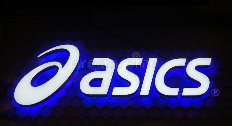 Blauw het neonteken van het Asicsembleem Asics is een Japanse multinationale onderneming die schoeisel en sportuitrusting produce royalty-vrije stock foto's