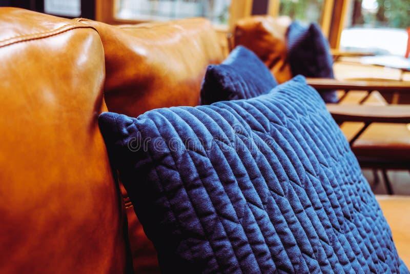 Blauw hoofdkussen op leerbank stock afbeeldingen