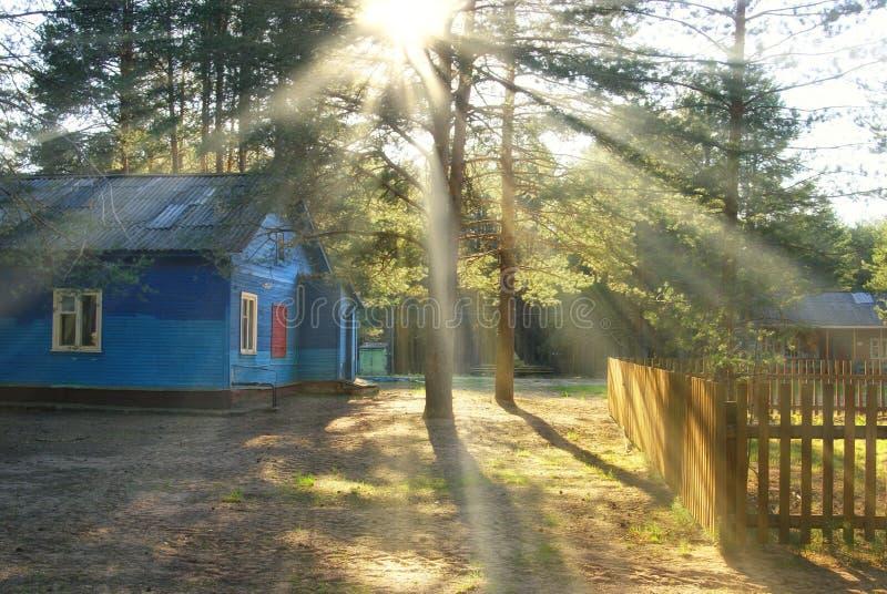 Blauw houten plattelandshuisjehuis met zon royalty-vrije stock afbeelding
