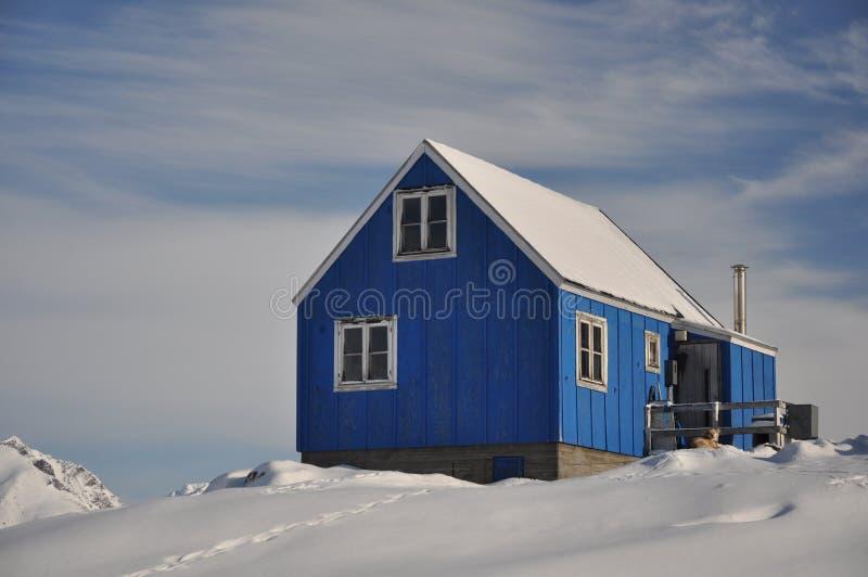 Blauw huis dat door sneeuw wordt behandeld stock afbeeldingen