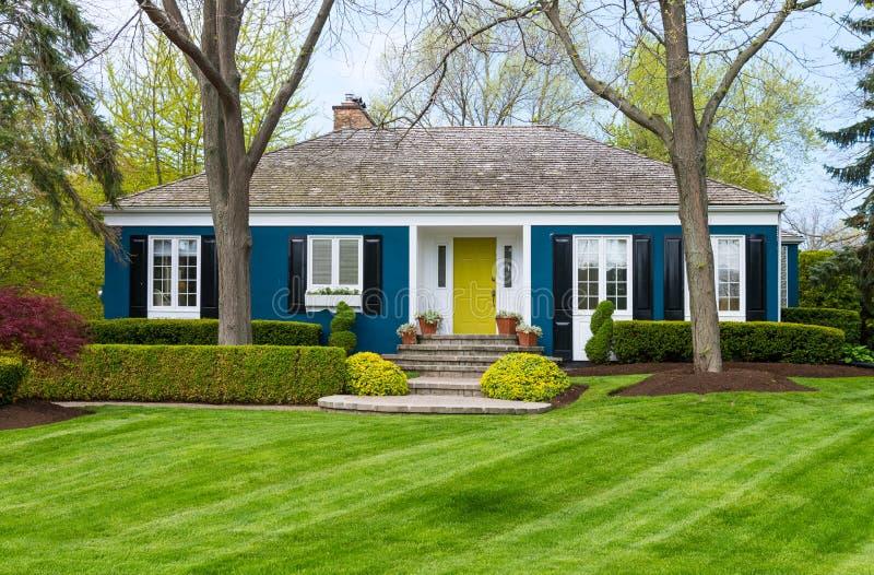 Blauw huis op groen gazon stock foto