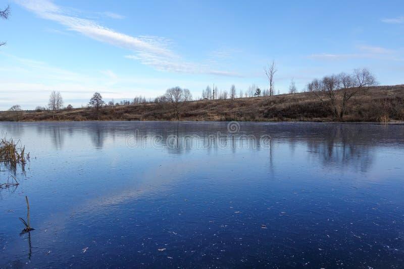 Blauw ijs op de oppervlakte van een bosmeer De sneeuw is nog niet gevallen De vroege Winter stock foto's