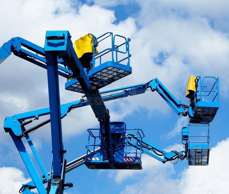 Blauw luchtplatform van kersenplukkers omhoog in de lucht tegen blauwe hemel en wolken royalty-vrije stock afbeelding