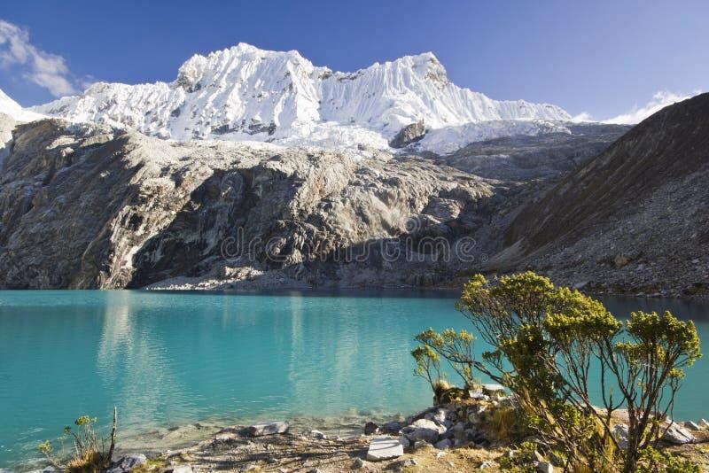Blauw meer in voet van snow-covered berg bij zonsopgang royalty-vrije stock foto
