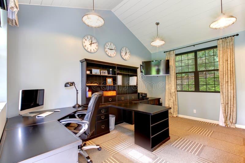 Blauw modern huisbureau met donker bruin meubilair. stock afbeelding