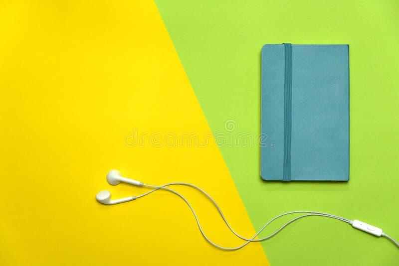 Blauw notaboek met witte oortelefoon op groene gele onderwijs kleurrijke achtergrond royalty-vrije stock fotografie