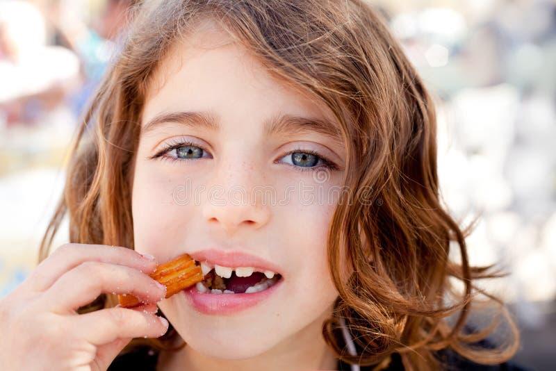 Blauw ogenmeisje dat gebraden crullers eet stock fotografie
