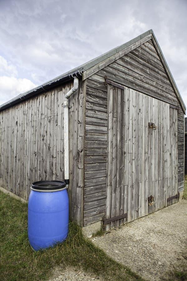 Blauw plastic wateruiteinde in bijlage aan houten loods stock fotografie