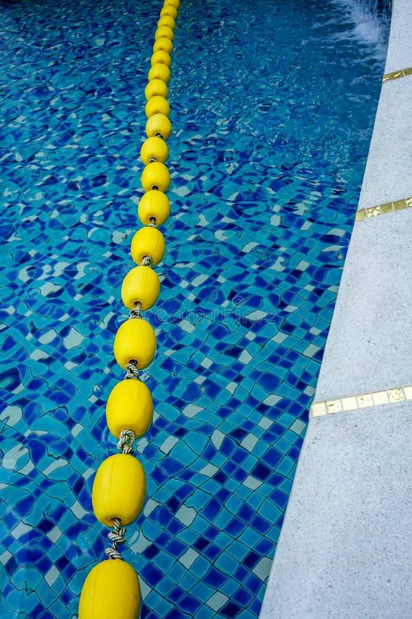 Blauw poolwater en gele zwemmende steegteller in zwembad stock foto's