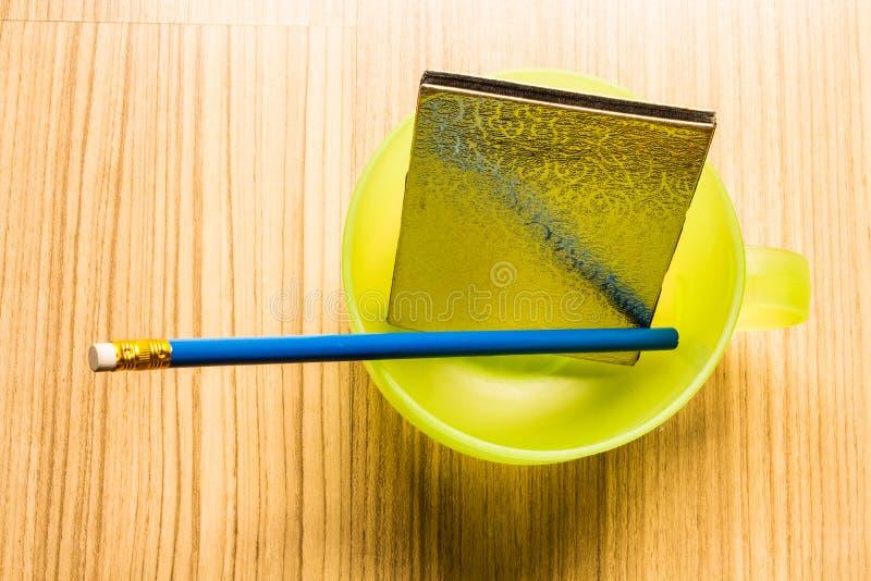 Blauw potlood en notitieboekje in een kop stock afbeeldingen