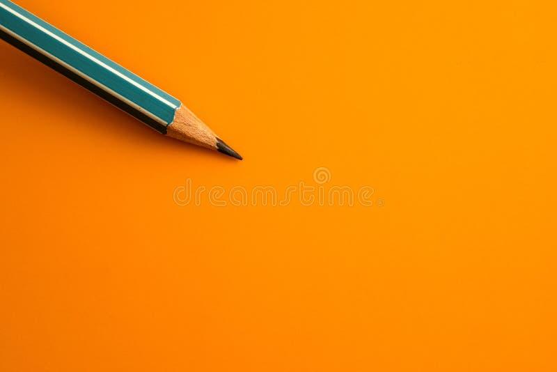 Blauw potlood op een geeloranje achtergrond, creatieve innovatie i royalty-vrije stock foto's