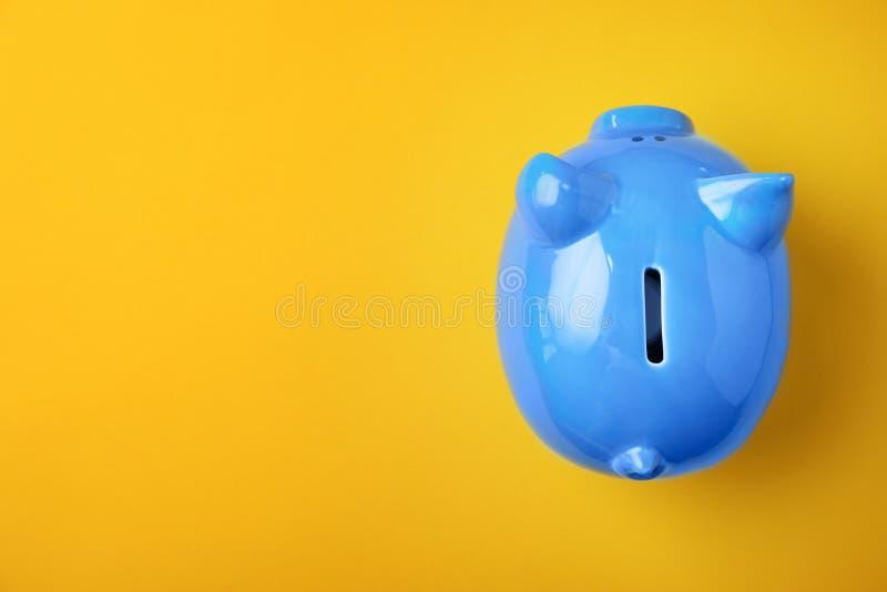Blauw spaarvarken op kleurenachtergrond stock foto's