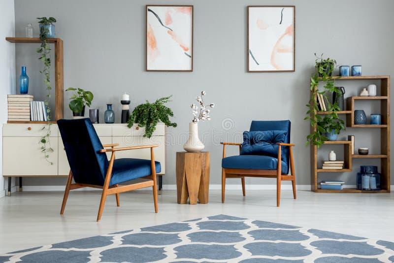 Blauw tapijt in grijs woonkamerbinnenland met affiches en houten lijst tussen leunstoelen royalty-vrije stock fotografie