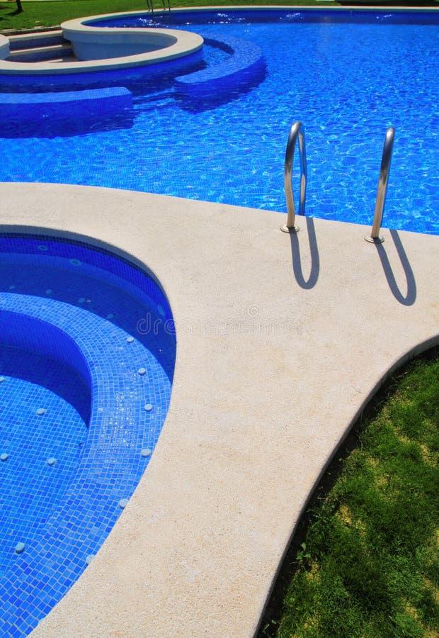 Blauw tegels zwembad met groene grastuin royalty-vrije stock afbeeldingen