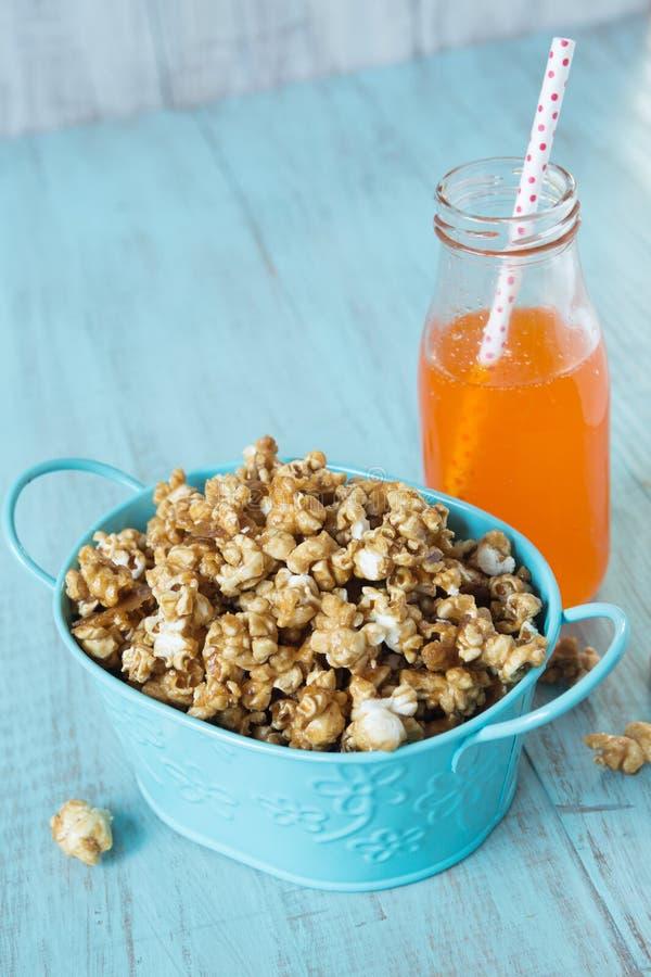 Blauw Tin With Caramel Popcorn en Oranje Frisdranksnack stock foto