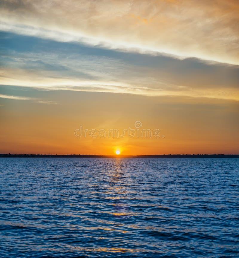 Blauw water in rivier en oranje zonsondergang in wolken stock fotografie