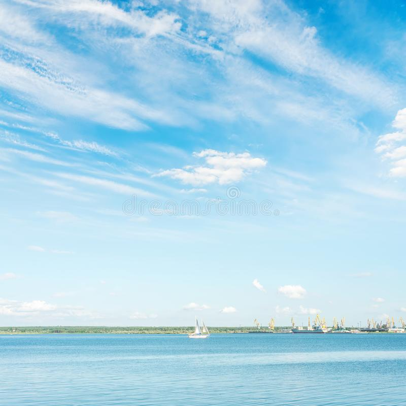Blauw water in rivier met boot en wolken stock foto's