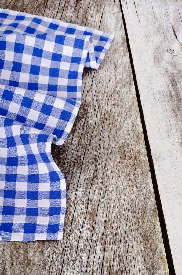 Blauw-wit geruit tafelkleed in oude houten stock afbeeldingen