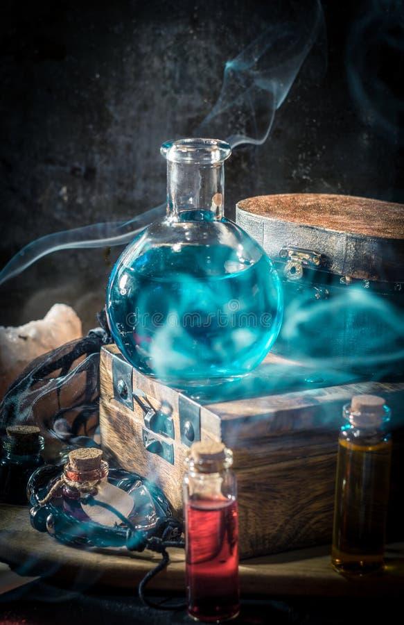 Blauw wondermiddel met rook Magisch concept stock afbeelding
