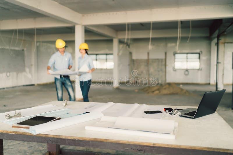 Blauwdruk, laptop computer, en industriële hulpmiddelen bij bouwwerf met twee ingenieurs of architecten die op achtergrond werken stock afbeelding