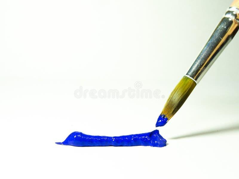 Blauwe acrylverf op de borstel en op een blad van document royalty-vrije stock fotografie