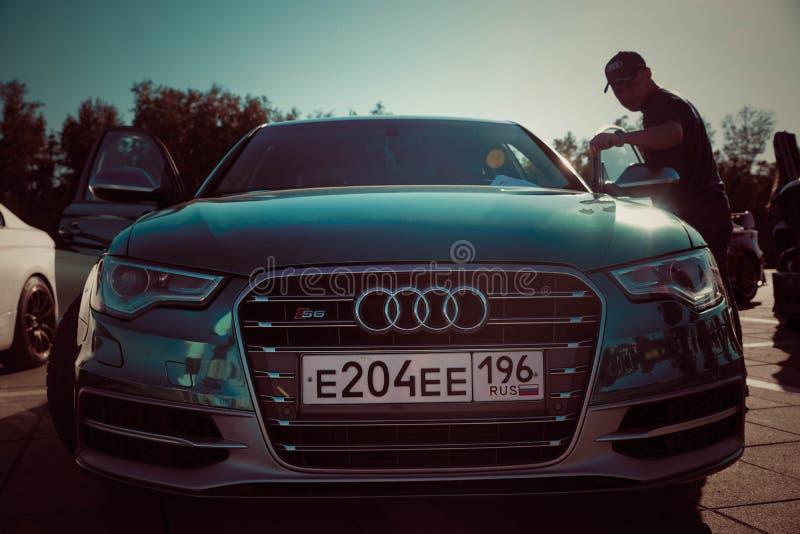 Blauwe auto en een mens bij de tentoonstelling van auto's in Rusland in de zomer royalty-vrije stock afbeeldingen