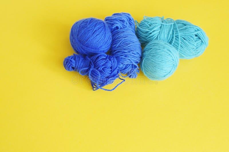 Blauwe bal van wollen draad Gele achtergrond De mening vanaf de bovenkant stock foto