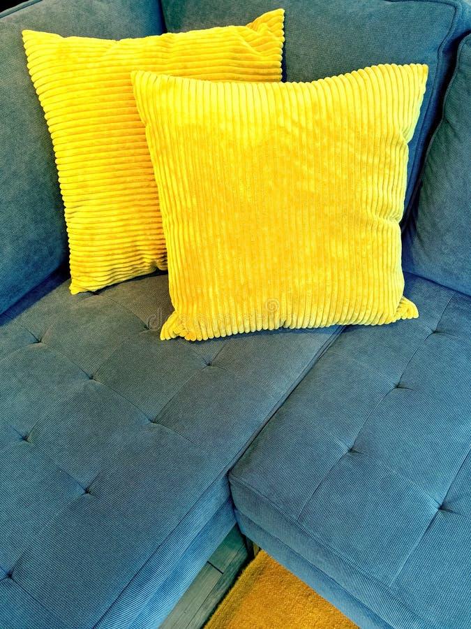 Blauwe bank met heldere gele kussens stock fotografie