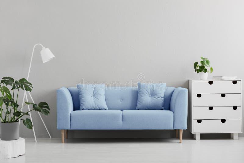 Blauwe bank tussen wit lamp en kabinet in grijze woonkamer int. stock fotografie