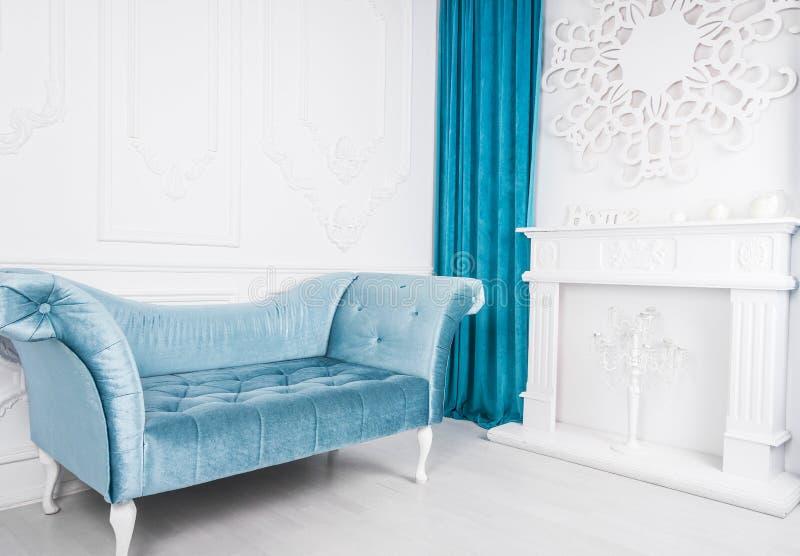 Blauwe bank in witte binnenlandse en grijze vloer Venetiaanse stijl Decoratieve open haard royalty-vrije stock fotografie