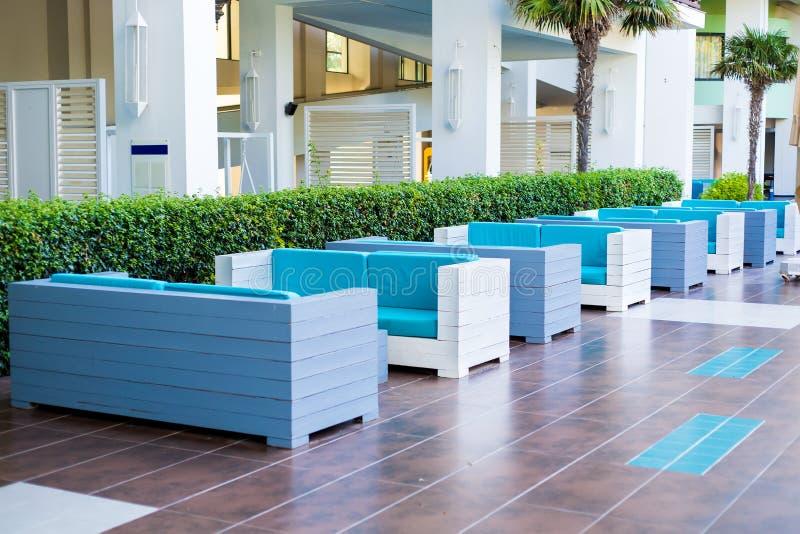 Blauwe banken op een rij openlucht in het halhotel, achtergrond van keurige groene ruimten stock foto's