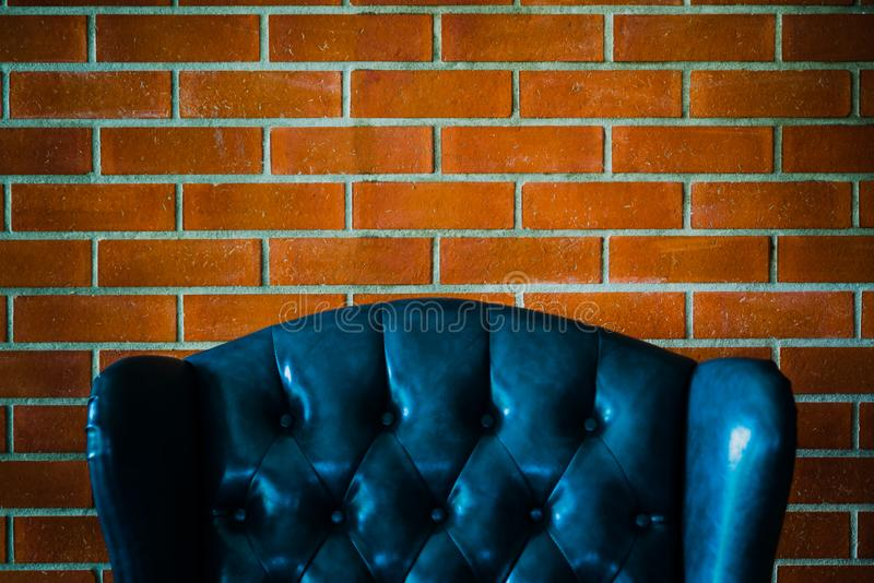 Blauwe beklede bank op een bakstenen muur backgrund uitstekende industri stock foto