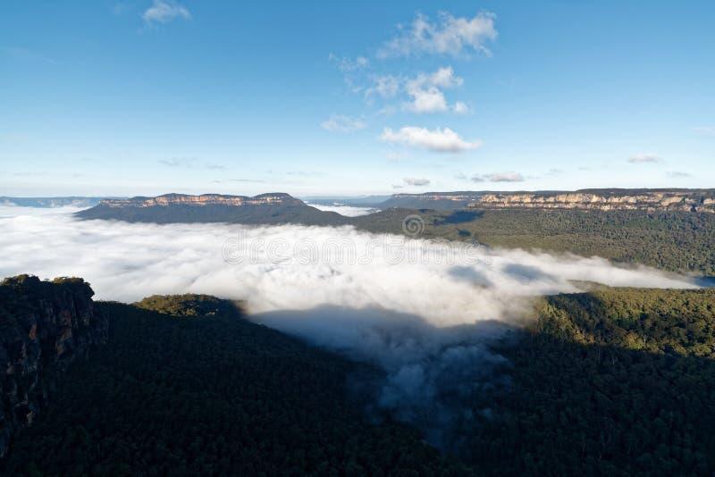 Blauwe berg met een overzees van wolken stock afbeeldingen